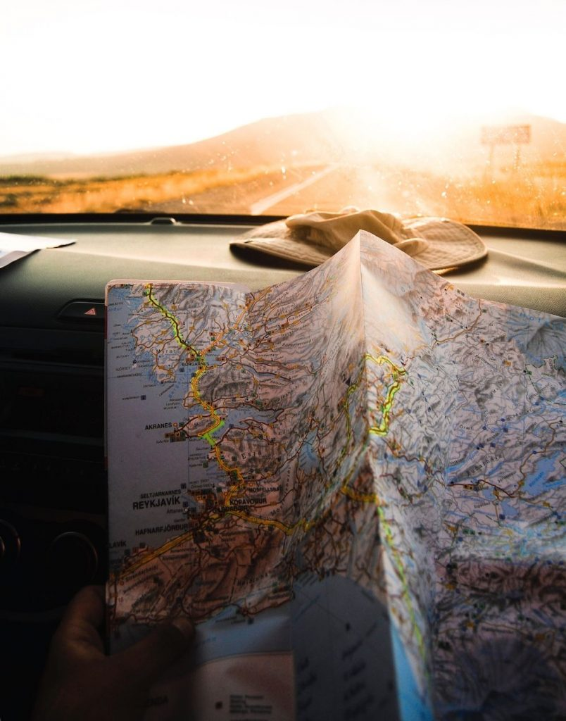 An open map on the dashboard of a car